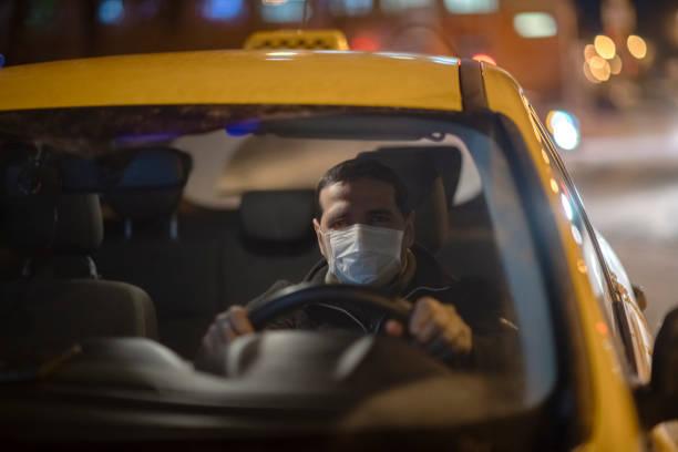 Taxifahrer trägt medizinische Schutzmaske auf einer Stadtstraße in der Nacht – Foto