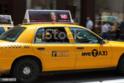 New York City, USA - May 21, 2011: New York City Taxi passing people on fifth avenue.