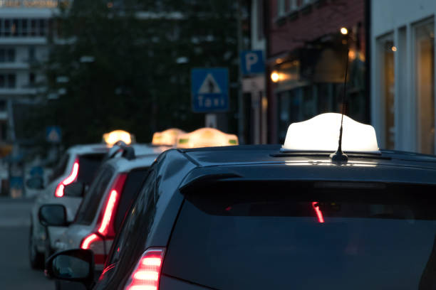 A taxi sign on the roof of a car at the city center of Tromso, Norway. stock photo