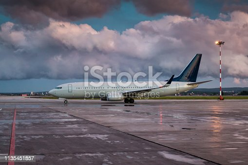 Taxiing a passenger aircraft on the airport apron on an overcast evening after rain