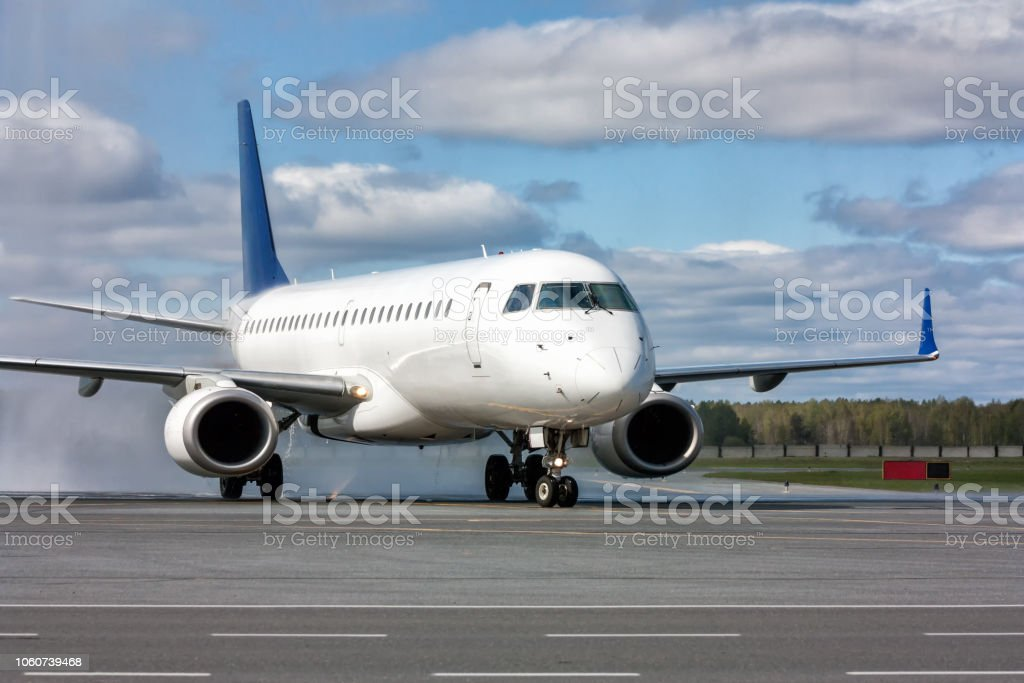 Taxiing a white passenger jet plane after passing through a water arch стоковое фото