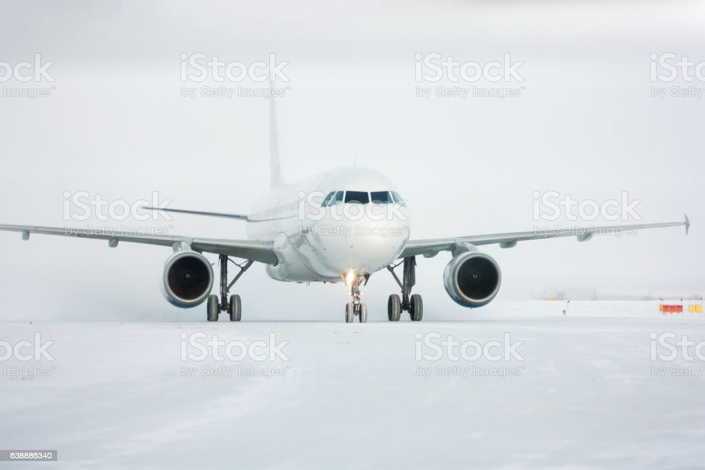 Taxiing passenger airplane in a snow blizzard стоковое фото