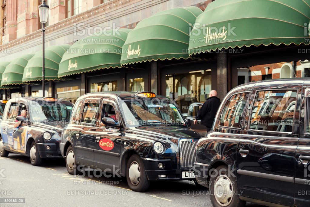 Taxis waiting in a queue outside Harrods in London stock photo