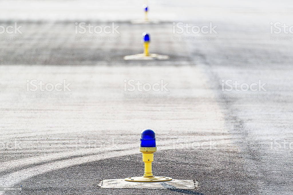 Taxiway light lamp with runway holding position line stock photo