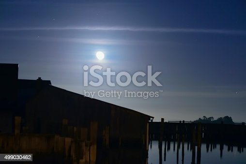 The boathouses at Taylors Landing as a full moon rises on a humid hazy night in the fall with a tinge of blue sky remaining broken up by wispy clouds
