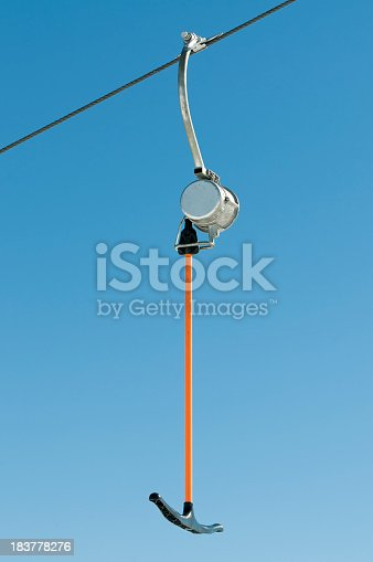 A single T-bar suspended from a metal cable at a ski resort.  Clear sky background.
