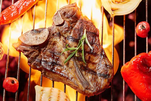 T-Bon bistec a la plancha con verduras. Carne frita en el fuego de la barbacoa - foto de stock