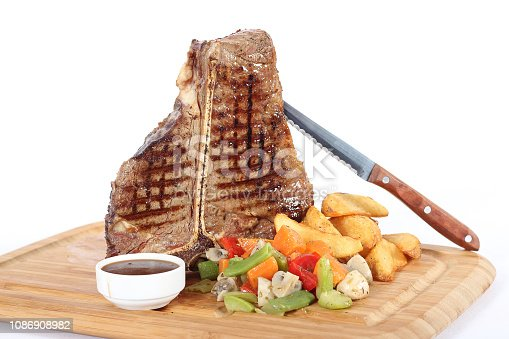 T-bone steak with garniture on wooden plate