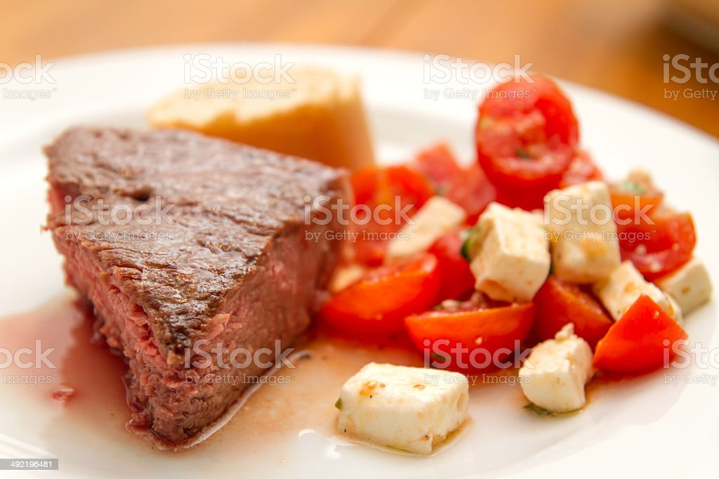 t-bone steak with tomatoes and feta cheese stock photo