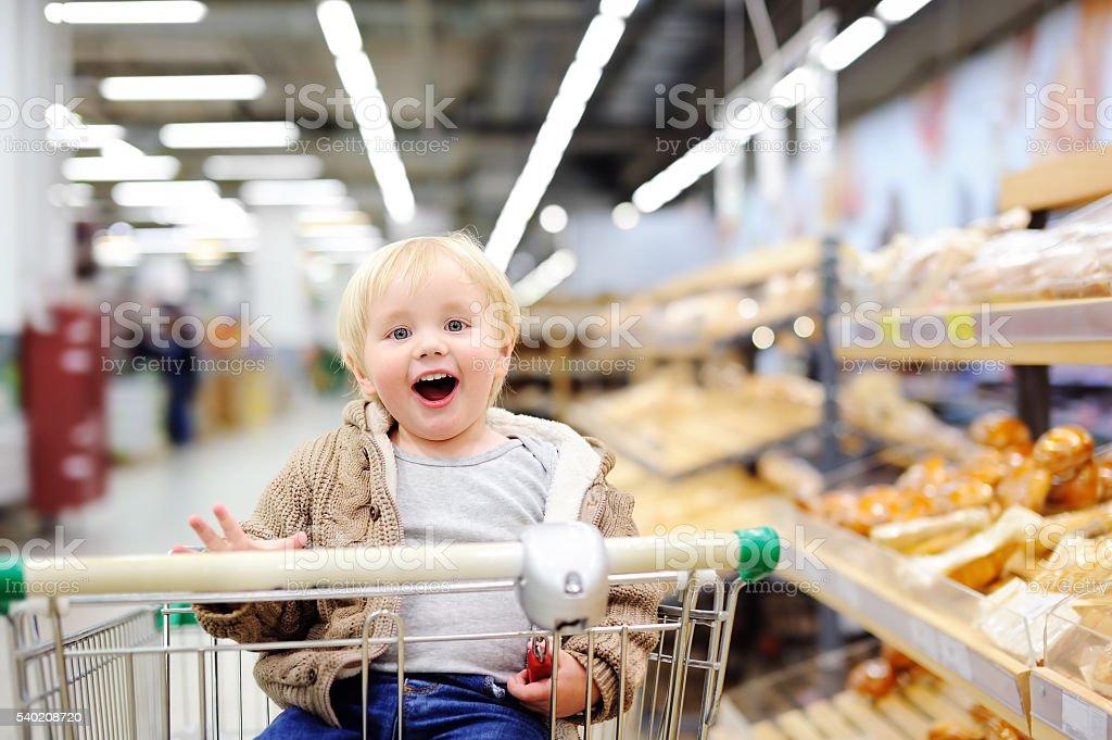 Tddler ragazzo seduto nel carrello della spesa del supermercato - foto stock