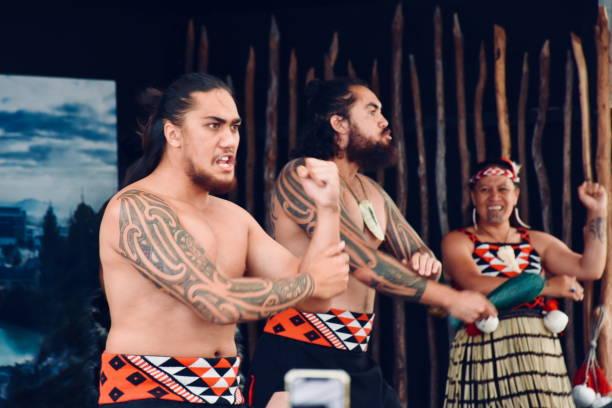 Te Pākira Cultural Performance at Whakarewarewa, The Living Maori Village, Rotorua, New Zealand/ Aotearoa Rotorua Bay of Plenty, NZ - December 28, 2018:   A traditional Maori Cultural Performance by Rotorua's Kapa Haka group Te Pākira at Whakarewarewa, The Living Maori Village in Rotorua, New Zealand/ Aotearoa's North Island.  Here members of the Tūhourangi Ngāti Wāhiao tribe perform a traditional Hake or Ceremonial War Challenge from Maori History to tourists watching the show in the Cultural Performance area of Whakarewarewa, The Living Maori Village. whakarewarewa stock pictures, royalty-free photos & images