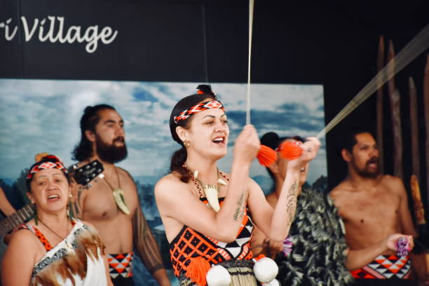 Te Pākira Cultural Performance at Whakarewarewa, The Living Maori Village, Rotorua, New Zealand/ Aotearoa Rotorua Bay of Plenty, NZ - December 28, 2018:   A traditional Maori Cultural Performance by Rotorua's Kapa Haka group Te Pākira at Whakarewarewa, The Living Maori Village in Rotorua, New Zealand/ Aotearoa's North Island.  Here members of the Tūhourangi Ngāti Wāhiao tribe perform Poi Dancing and sing a traditional song or Waiata of Maori History to tourists watching the show in the Cultural Performance area of Whakarewarewa, The Living Maori Village. whakarewarewa stock pictures, royalty-free photos & images