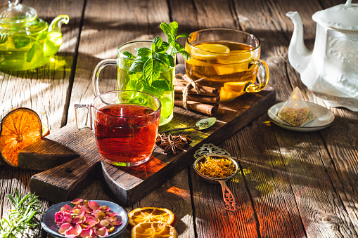 Tea and herbal infusion with dried herbs on wooden rustic table board, including calendula, rose petals, mint leaves, cinnamon sticks, dried orange slices, with mint tea, ginger lemon tea and black tea.