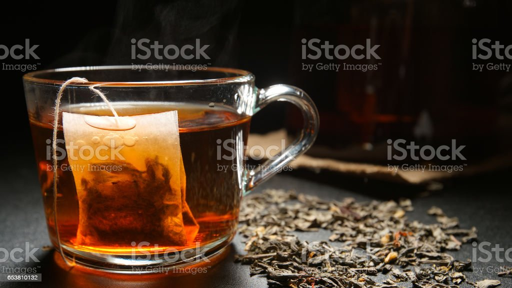 Tea bag in a hot tea cup on a table stock photo
