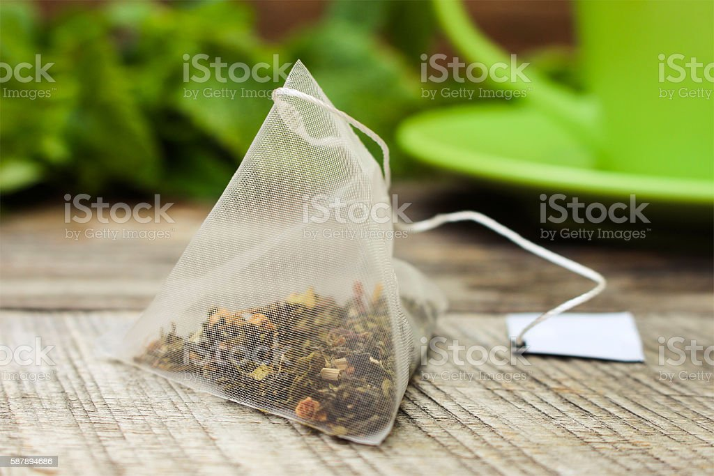 Tea bag on background of mint and and green cup stock photo
