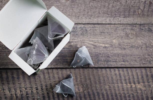 teebeutel form pyramide in papier verpackung box auf holztisch hintergrund. draufsicht mit textfreiraum. - pyramide sammlung stock-fotos und bilder