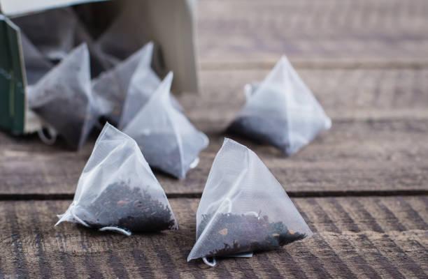 teebeutel form pyramide auf holztisch hintergrund. draufsicht mit textfreiraum. - pyramide sammlung stock-fotos und bilder