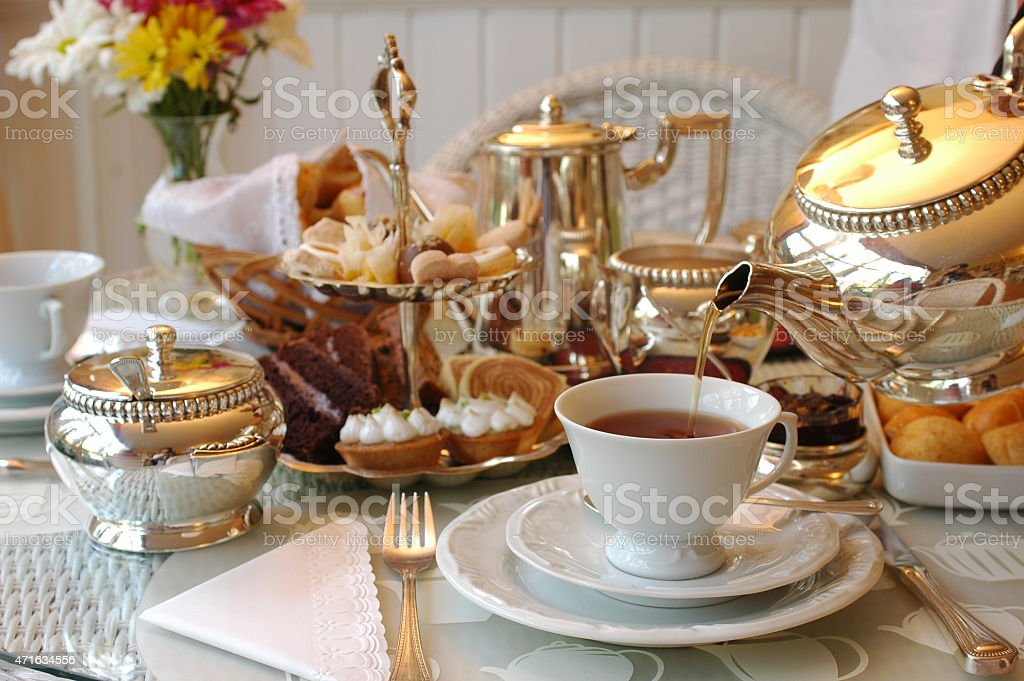 Tea being poured into a cup on a table set for afternoon tea stock photo