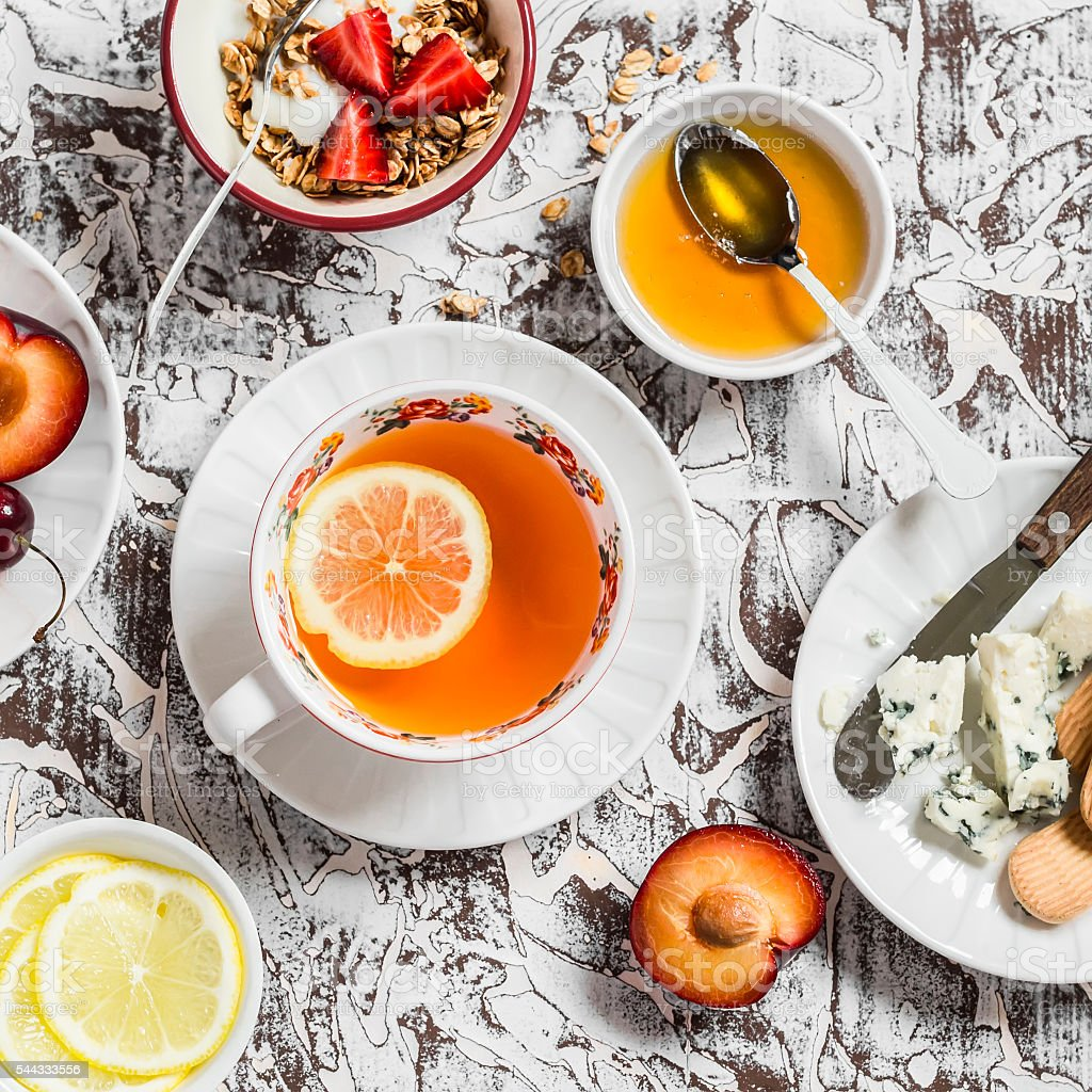 Tea, blue cheese, biscuits, honey, yogurt with granola and fruit stock photo