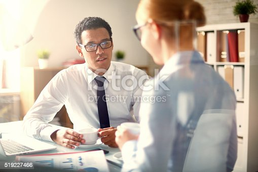 Young businessman in eyeglasses talking to colleague at coffee break
