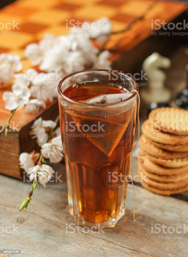 tea brew in a cup (tea bag) on a wooden table and flowering spring twigs. stock photo