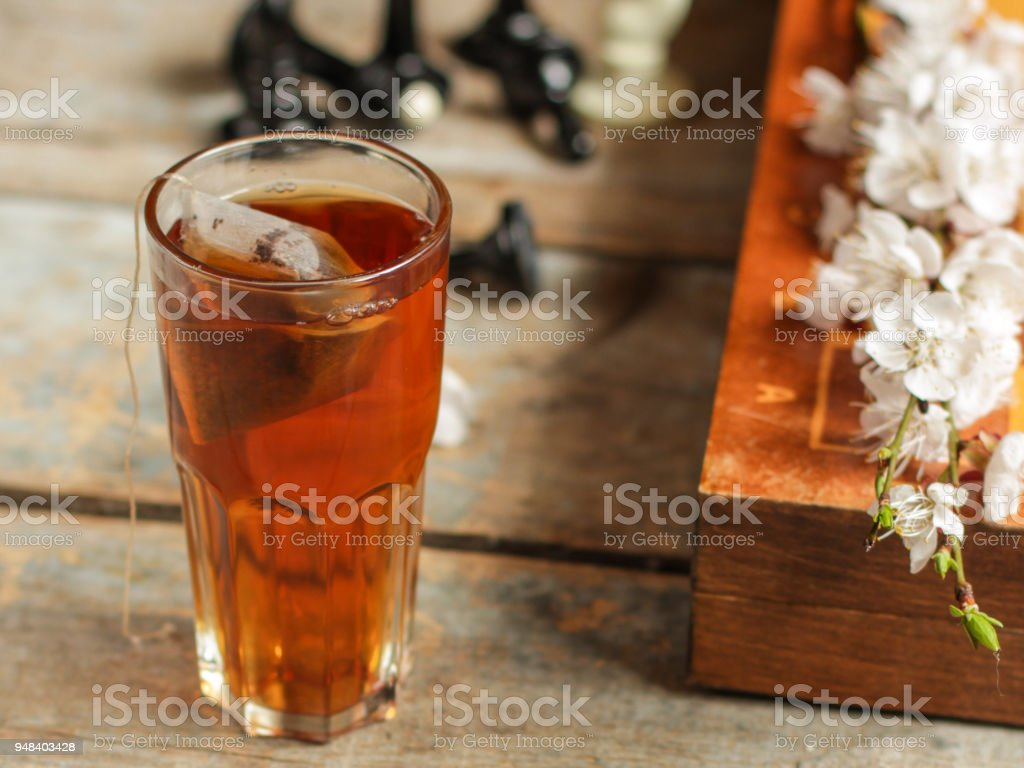 tea brew in a cup (tea bag) on the table and flowering spring twigs. Food background - drink background stock photo
