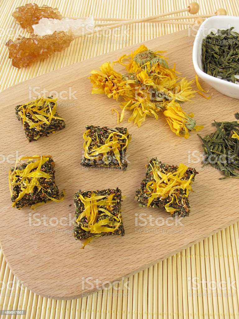 Tea bricks made of pressed green and marigold flowers stock photo