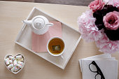 Directly above shot of tea, foam candies, flower arrangement and books on coffee table in.