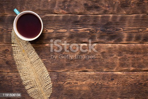 Hot tea cup and golden leaf on brown wooden table flat lay background with copy space.