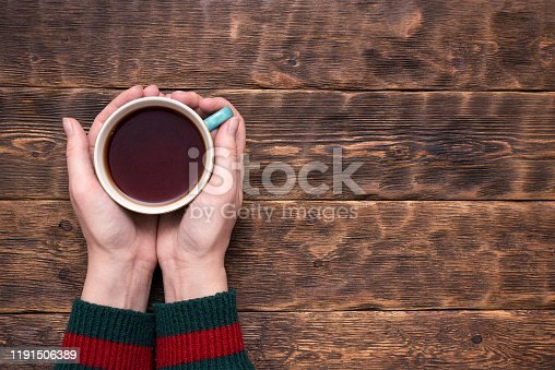 Female hands in sweater with a cup of hot tea above wooden table background with copy space.