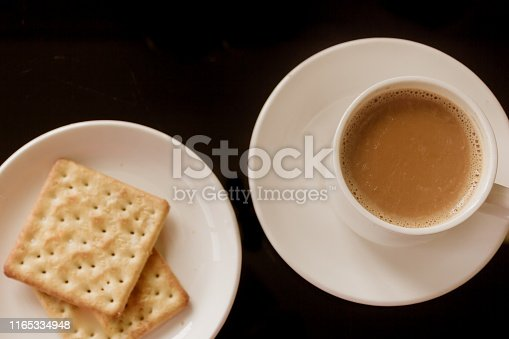 Tea cup and plate with stack of cream cracker biscuits isolated black background. Top View. Close up picture. Chinese tea cup, tasty biscuit cookies. Traditional hot drink for breakfast. Herbal tonic.