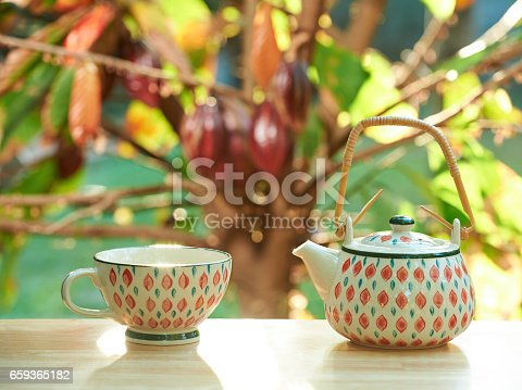 istock Tea cup and pot on sunny day light 659365182