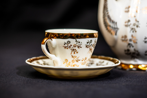 Studio table top shot of an antique tea cup and saucer with shallow depth-of-field.