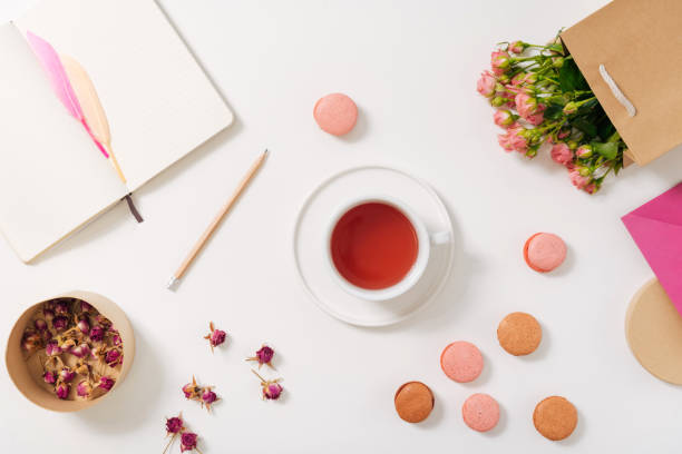 tea cup being surrounded by macaroons - rosen tee stock-fotos und bilder