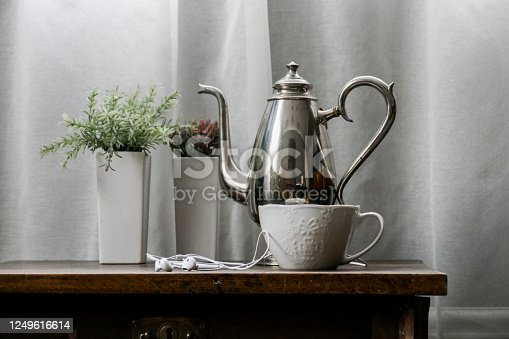 White tea cup, teapot and flowers on vintage table in front of white curtain as background, close-up