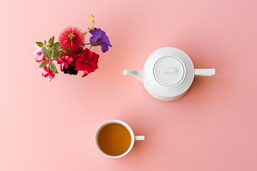 Tea cup, pot and flowers on pink background from above