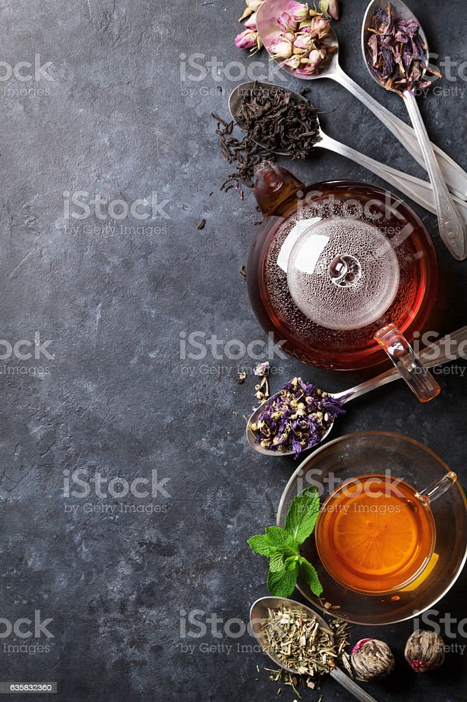 Tea cup, teapot and assortment of dry tea in spoons stock photo