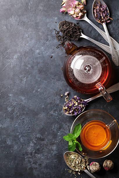 tea cup, teapot and assortment of dry tea in spoons - rosen tee stock-fotos und bilder