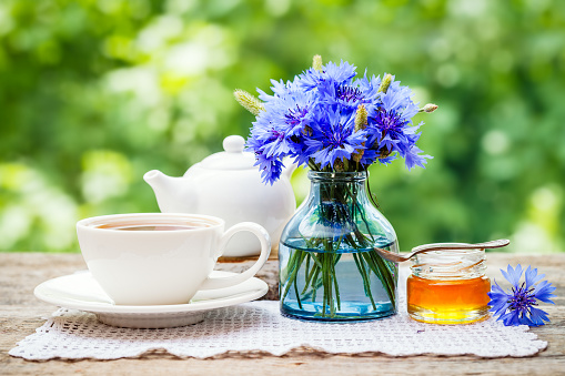 Tea cup, teapot, honey and summer bouquet of blue cornflower