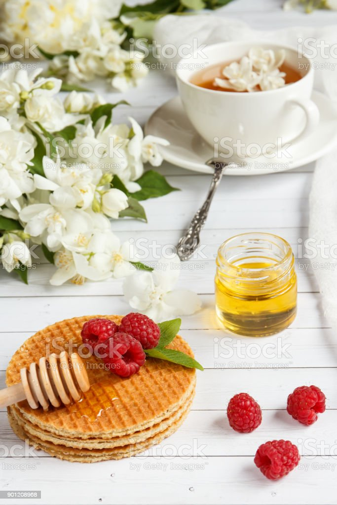 Tea Cup with Jasmine flowers and thin waffles with honey and raspberry on a light wooden background stock photo