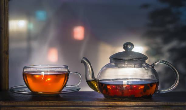 Tea cup with tea pot on the windowsill. Tea on a background of a night landscape. Tea time. stock photo