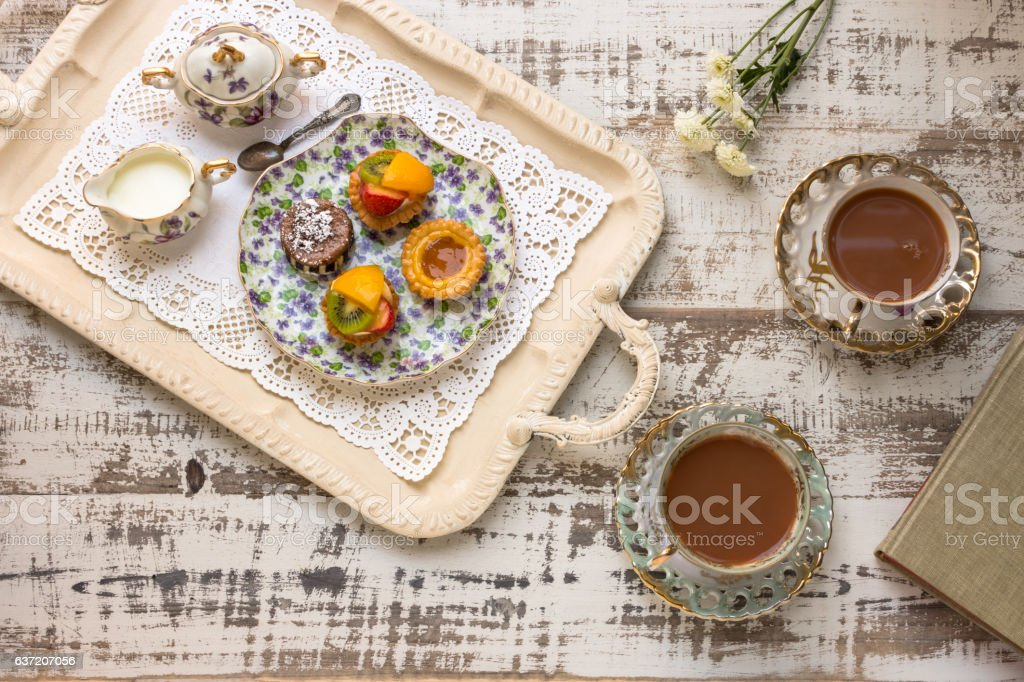 Tea cups and fruit tarts laid out on rustic table stock photo