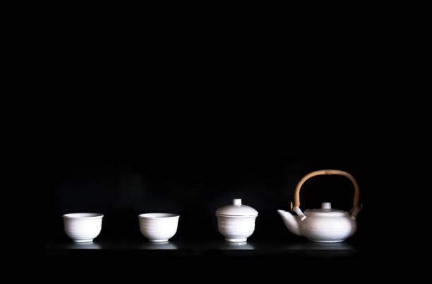 teetassen und teekanne auf schwarzem hintergrund, textfreiraum - keramikteekannen stock-fotos und bilder