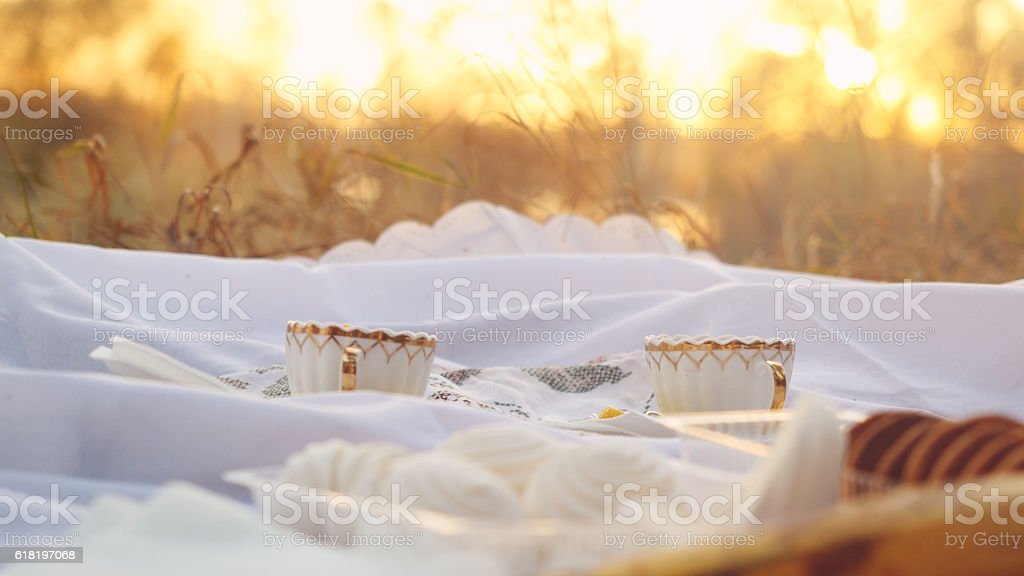 Tea cups outdoors at picnic during autumn with bokeh and stock photo