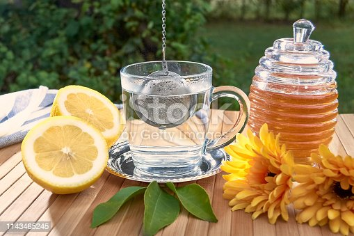 istock Tea filter ball falling into a glass of hot water. 1143465245
