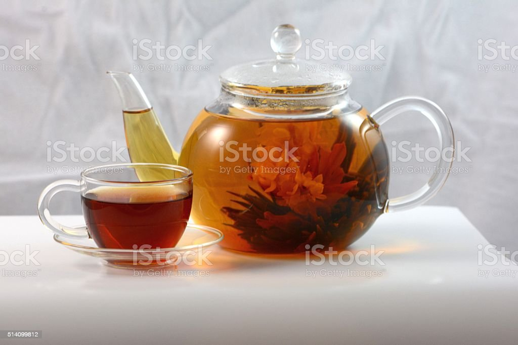 Tea Flower in a Glass Pot with Teacup on Saucer stock photo