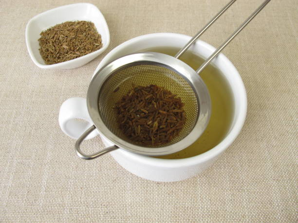Tea from caraway seeds and caraway fruits in the tea strainer stock photo