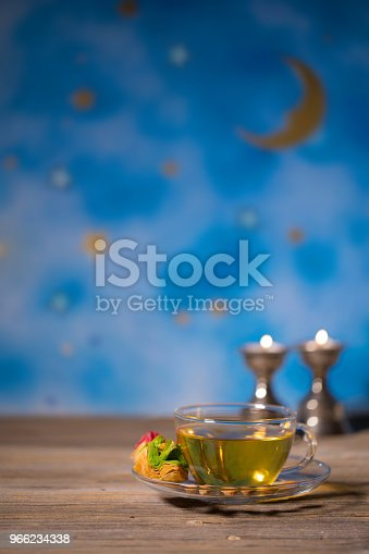 istock Tea in a glass cup with Arabic sweets on a wooden surface. 966234338
