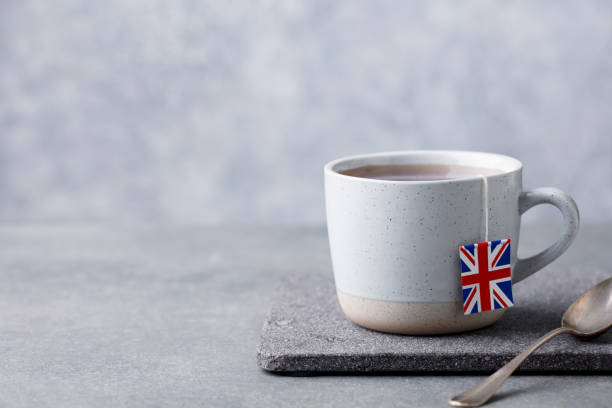 Tea in mug with British flag tea bag label. Grey background. Copy space. stock photo