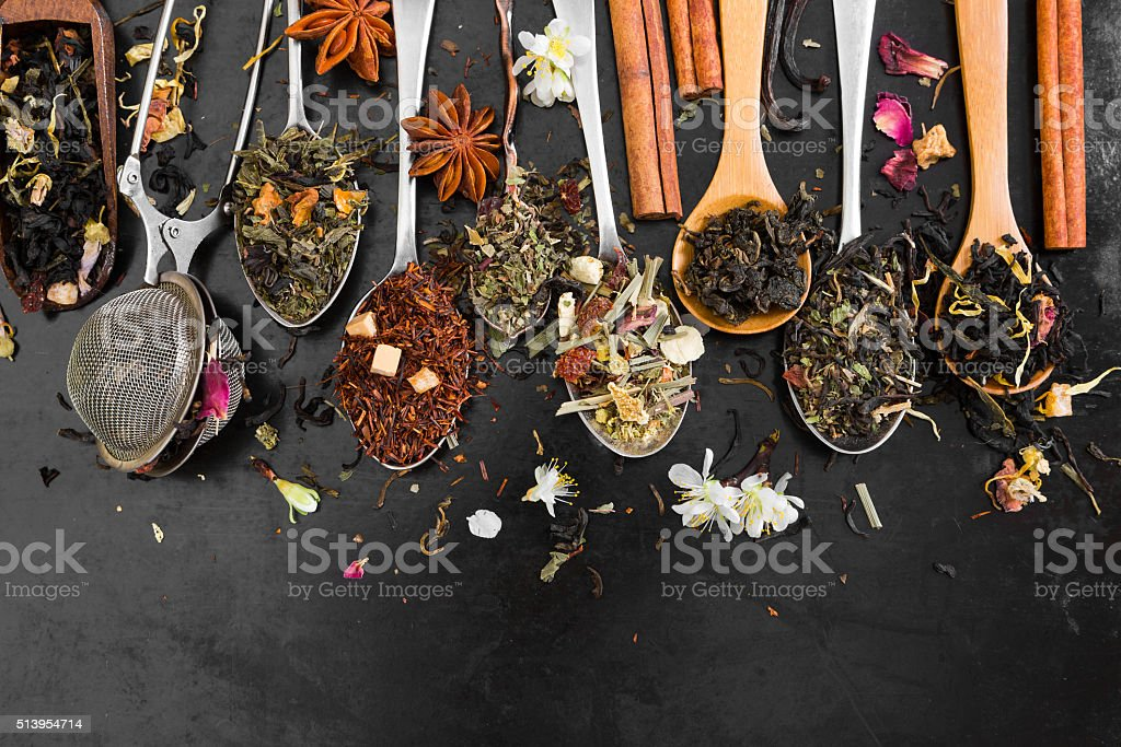 Tea in spoon on rustic black background. stock photo